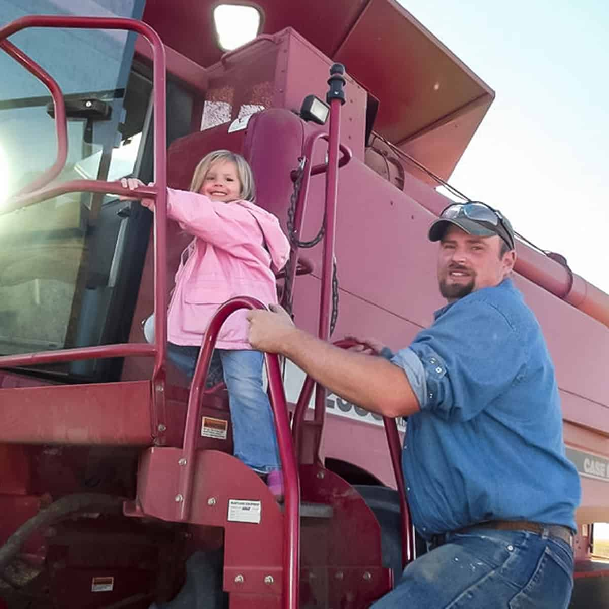 father-and-daughter-on-farm-equipment-in-rural-america